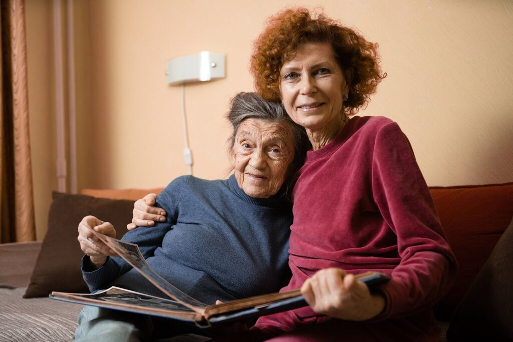 Senior woman and her adult daughter looking at photo album together on couch in living room, talking joyful discussing memories. Weekend with parents, family day, thanksgiving, moms holiday
