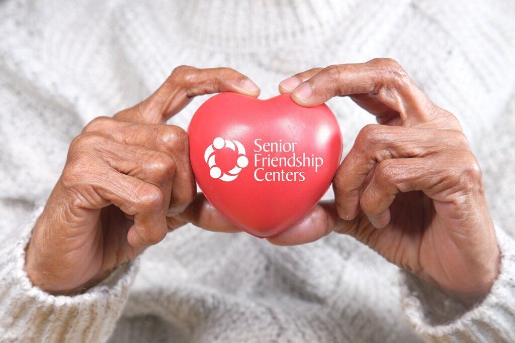 senior women holding red heart close up