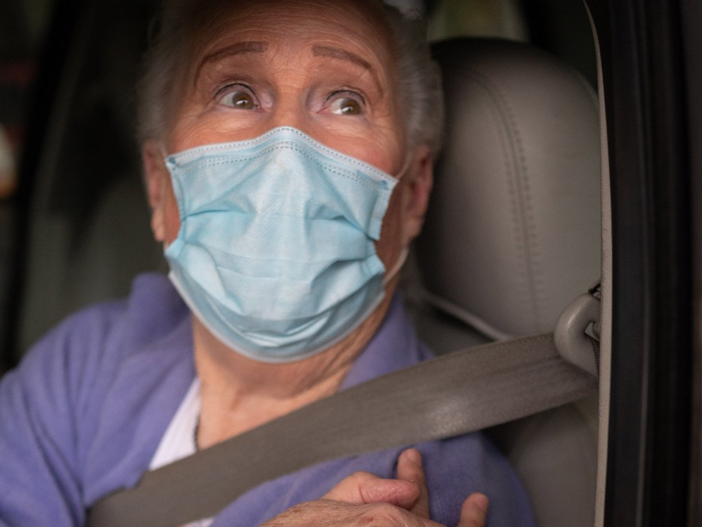 senior man with mask in car