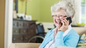Cheerful Caucasian senior woman smiles while talking on a smart phone. She is wearing a light blue cardigan and is sitting comfortably in her living room. She has gray hair and glasses.